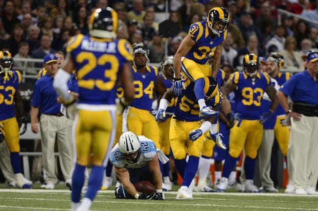 Nov 3, 2013; St. Louis, MO, USA; St. Louis Rams cornerback Cortland Finnegan (31) lands on the shoulders of outside linebacker Alec Ogletree (52) after leaping over Tennessee Titans fullback Collin Mooney (42) during the first half at the Edward Jones Dome. Tennessee defeated St. Louis 28-21. Mandatory Credit: Jeff Curry-USA TODAY Sports