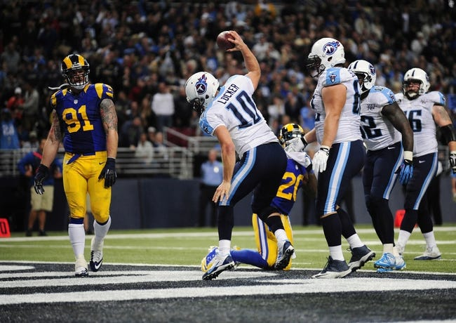Nov 3, 2013; St. Louis, MO, USA; Tennessee Titans quarterback Jake Locker (10) spikes the ball after running in for a five yard touchdown as St. Louis Rams defensive end Chris Long (91) looks on during the second half at the Edward Jones Dome. Tennessee defeated St. Louis 28-21. Mandatory Credit: Jeff Curry-USA TODAY Sports