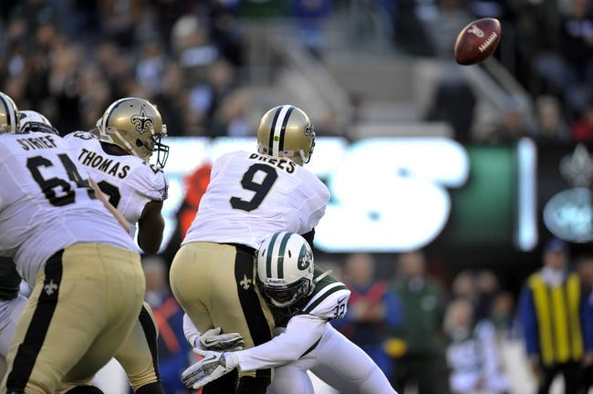 Nov 3, 2013; East Rutherford, NJ, USA; New Orleans Saints quarterback Drew Brees (9) is hit by New York Jets defensive back Josh Bush (32) as he releases a pass during the second half at MetLife Stadium. The Jets won the game 26-20. Mandatory Credit: Joe Camporeale-USA TODAY Sports