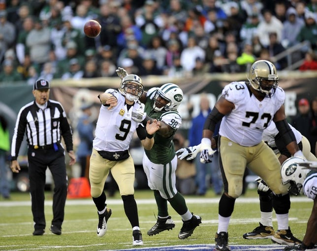Nov 3, 2013; East Rutherford, NJ, USA; New Orleans Saints quarterback Drew Brees (9) is hit by New York Jets outside linebacker Quinton Coples (98) as he throws a pass during the second half at MetLife Stadium. The Jets won the game 26-20. Mandatory Credit: Joe Camporeale-USA TODAY Sports