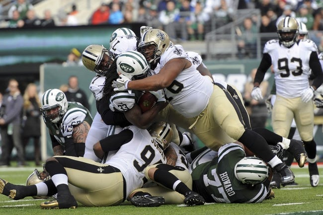 Nov 3, 2013; East Rutherford, NJ, USA; New York Jets running back Chris Ivory (33) is met by New Orleans Saints defenders at the line of scrimmage during the first half at MetLife Stadium. The Jets won the game 26-20. Mandatory Credit: Joe Camporeale-USA TODAY Sports