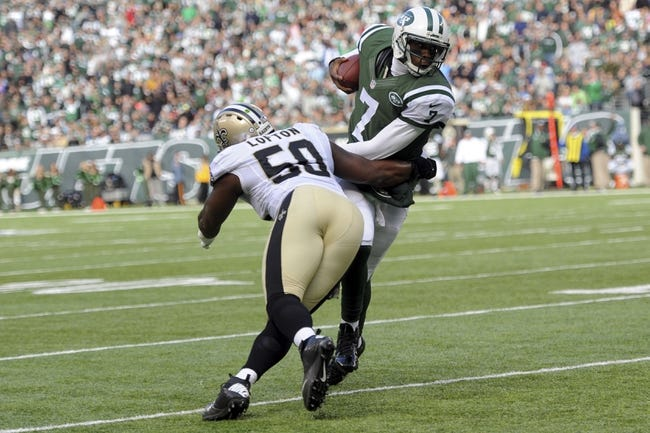 Nov 3, 2013; East Rutherford, NJ, USA; New York Jets quarterback Geno Smith (7) attempts to slip away from New Orleans Saints middle linebacker Curtis Lofton (50) during the first half at MetLife Stadium. The Jets won the game 26-20. Mandatory Credit: Joe Camporeale-USA TODAY Sports