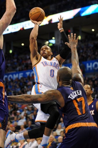 Nov 3, 2013; Oklahoma City, OK, USA; Oklahoma City Thunder point guard Russell Westbrook (0) attempts a shot against Phoenix Suns small forward P.J. Tucker (17) during the third quarter at Chesapeake Energy Arena. Mandatory Credit: Mark D. Smith-USA TODAY Sports