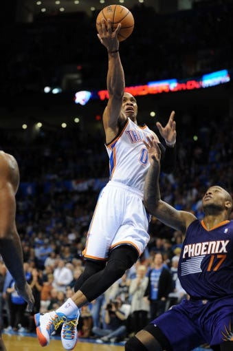 Nov 3, 2013; Oklahoma City, OK, USA; Oklahoma City Thunder point guard Russell Westbrook (0) attempts a shot against Phoenix Suns small forward P.J. Tucker (17)during the fourth quarter at Chesapeake Energy Arena. Mandatory Credit: Mark D. Smith-USA TODAY Sports