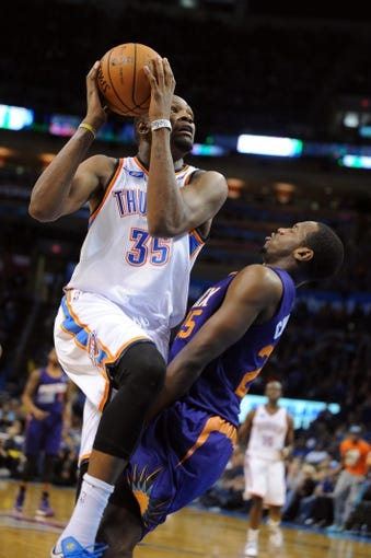 Nov 3, 2013; Oklahoma City, OK, USA; Oklahoma City Thunder small forward Kevin Durant (35) attempts a shot against Phoenix Suns shooting guard Dionte Christmas (25) during the fourth quarter at Chesapeake Energy Arena. Mandatory Credit: Mark D. Smith-USA TODAY Sports