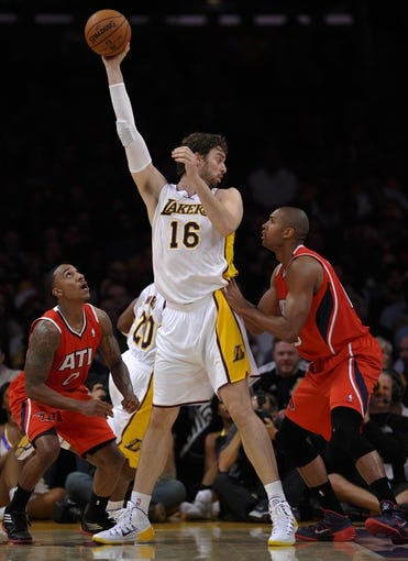Nov 3, 2013; Los Angeles, CA, USA; Los Angeles Lakers power forward Pau Gasol (16) looks for a teammate to pass off to on the baseline as Atlanta Hawks point guard Jeff Teague (0) and Atlanta Hawks center Al Horford (15) defend at Staples Center. Mandatory Credit: Robert Hanashiro-USA TODAY Sports