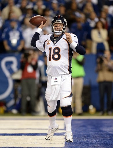 Oct 20, 2013; Indianapolis, IN, USA; Denver Broncos quarterback Peyton Manning (18) prepares to pass from the end zone in the second quarter against the Indianapolis Colts at Lucas Oil Stadium. The Colts defeated the Broncos 39-33. Mandatory Credit: Ron Chenoy-USA TODAY Sports