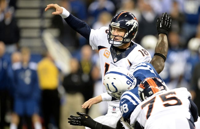 Oct 20, 2013; Indianapolis, IN, USA; Denver Broncos quarterback Peyton Manning (18) is hit by Indianapolis Colts outside linebacker Robert Mathis (98) as tackle Chris Clark (75) attempts to block in the fourth quarter at Lucas Oil Stadium. The Colts defeated the Broncos 39-33. Mandatory Credit: Ron Chenoy-USA TODAY Sports