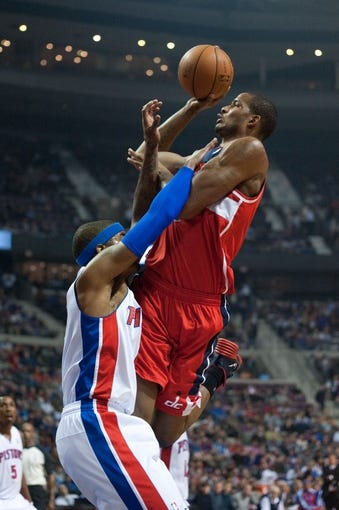 Oct 30, 2013; Auburn Hills, MI, USA; Detroit Pistons small forward Josh Smith (6) draws a foul as Washington Wizards small forward Trevor Ariza (1) drives to the basket during the first quarter at The Palace of Auburn Hills. Mandatory Credit: Tim Fuller-USA TODAY Sports