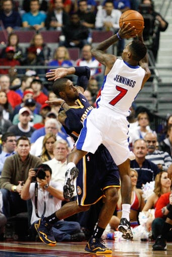 Nov 5, 2013; Auburn Hills, MI, USA; Detroit Pistons point guard Brandon Jennings (7) draws a foul against Indiana Pacers point guard C.J. Watson (32) during the third quarter at The Palace of Auburn Hills. The Pacers beat the Pistons 99-91. Mandatory Credit: Raj Mehta-USA TODAY Sports