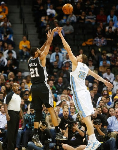 Nov 5, 2013; Denver, CO, USA; San Antonio Spurs forward Tim Duncan (21) shoots the ball over Denver Nuggets center Timofey Mozgov (25) during the first half at Pepsi Center. Mandatory Credit: Chris Humphreys-USA TODAY Sports