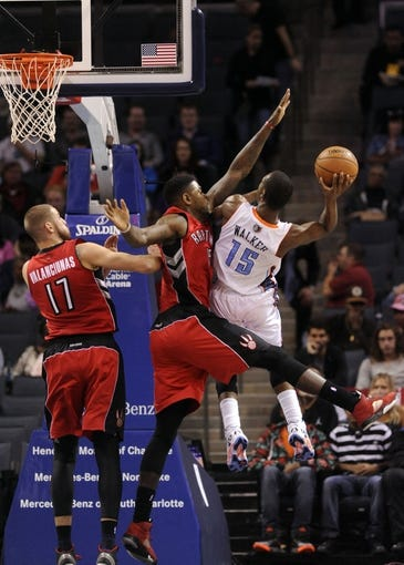 Nov 6, 2013; Charlotte, NC, USA; Charlotte Bobcats guard Kemba Walker (15) drives to the basket as he is defended by Toronto Raptors forward Amir Johnson (15) and center Jonas Valanciunas (17) during the game at Time Warner Cable Arena. Mandatory Credit: Sam Sharpe-USA TODAY Sports