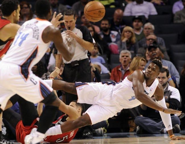 Nov 6, 2013; Charlotte, NC, USA; Charlotte Bobcats forward Jeff Adrien (4) passes the ball to forward Michael Kidd-Gilchrist (14) as he stumbles and falls during the game at Time Warner Cable Arena. Mandatory Credit: Sam Sharpe-USA TODAY Sports