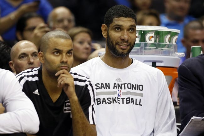 Nov 6, 2013; San Antonio, TX, USA; San Antonio Spurs guard Tony Parker (left) and forward Tim Duncan (right) watch the game against the Phoenix Suns from the bench during the first half at AT&T Center. Mandatory Credit: Soobum Im-USA TODAY Sports