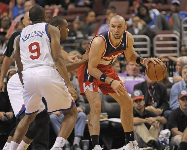Nov 6, 2013; Philadelphia, PA, USA; Washington Wizards center Marcin Gortat (4) backs in against Philadelphia 76ers power forward Lavoy Allen (50) and shooting guard James Anderson (9) during the second half at Wells Fargo Center. The Wizards defeated the 76ers, 116-102. Mandatory Credit: Eric Hartline-USA TODAY Sports