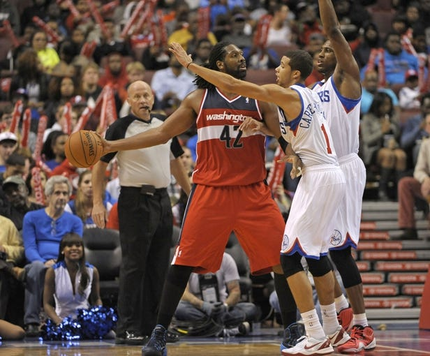 Nov 6, 2013; Philadelphia, PA, USA; Washington Wizards power forward Nene Hilario (42) looks to pass against Philadelphia 76ers point guard Michael Carter-Williams (1) and power forward Thaddeus Young (21) during the second half at Wells Fargo Center. The Wizards defeated the 76ers, 116-102. Mandatory Credit: Eric Hartline-USA TODAY Sports