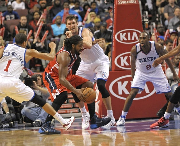 Nov 6, 2013; Philadelphia, PA, USA; Washington Wizards power forward Nene Hilario (42) drives against Philadelphia 76ers point guard Michael Carter-Williams (1), center Spencer Hawes (00) and shooting guard James Anderson (9)  during the second half at Wells Fargo Center. The Wizards defeated the 76ers, 116-102. Mandatory Credit: Eric Hartline-USA TODAY Sports