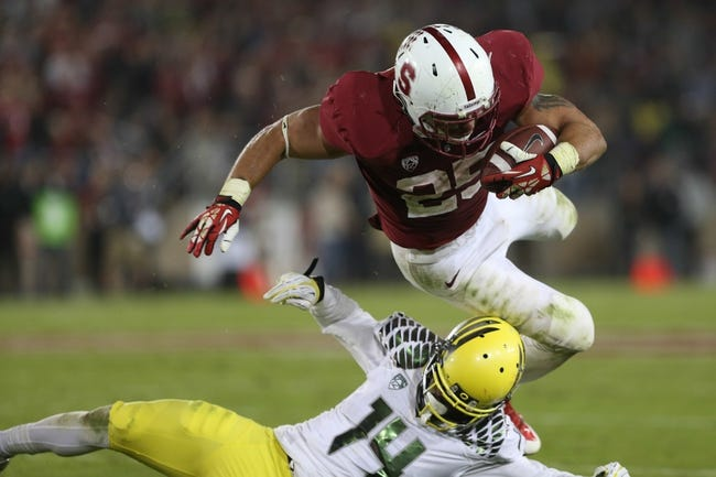 Nov 7, 2013; Stanford, CA, USA; Oregon Ducks cornerback Ifo Ekpre-Olomu (14) tackles Stanford Cardinal running back Tyler Gaffney (25) during the fourth quarter at Stanford Stadium. The Stanford Cardinal defeated the Oregon Ducks 26-20. Mandatory Credit: Kelley L Cox-USA TODAY Sports