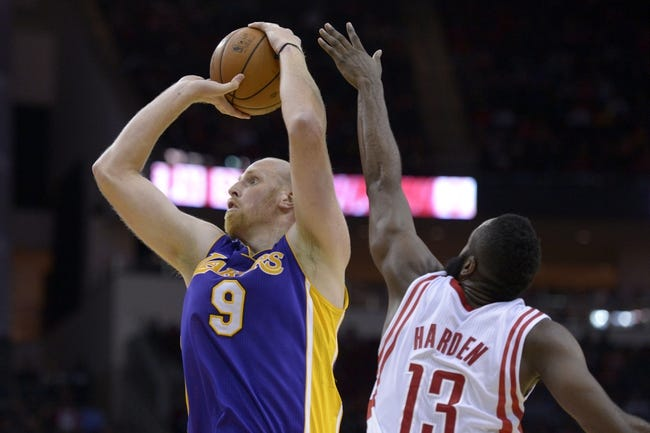 Nov 7, 2013; Houston, TX, USA; Los Angeles Lakers center Chris Kaman (9) shoots over Houston Rockets shooting guard James Harden (13) during the second half at Toyota Center. The Lakers won 99-98. Mandatory Credit: Thomas Campbell-USA TODAY Sports