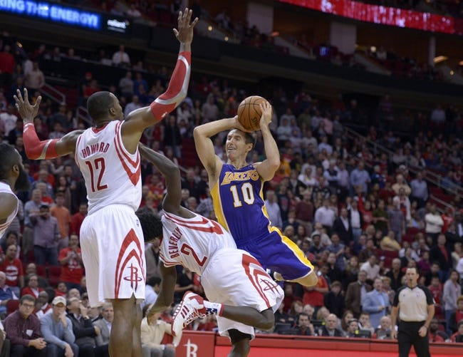 Nov 7, 2013; Houston, TX, USA; Los Angeles Lakers point guard Steve Nash (10) draws a foul on Houston Rockets point guard Patrick Beverley (2) during the second half at Toyota Center. The Lakers won 99-98. Mandatory Credit: Thomas Campbell-USA TODAY Sports
