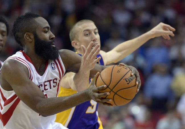 Nov 7, 2013; Houston, TX, USA; Houston Rockets shooting guard James Harden (13) and Los Angeles Lakers point guard Steve Blake (5) reach for a loose ball during the second half at Toyota Center. The Lakers won 99-98. Mandatory Credit: Thomas Campbell-USA TODAY Sports