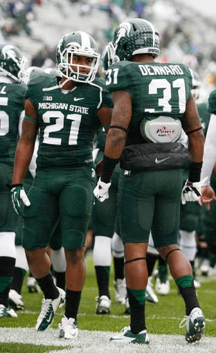 Nov 2, 2013; East Lansing, MI, USA; Michigan State Spartans cornerback Justin Williams (21) looks at cornerback Darqueze Dennard (31) before the game against the Michigan Wolverines at Spartan Stadium. The Spartans beat the Wolverines 29-6. Mandatory Credit: Raj Mehta-USA TODAY Sports
