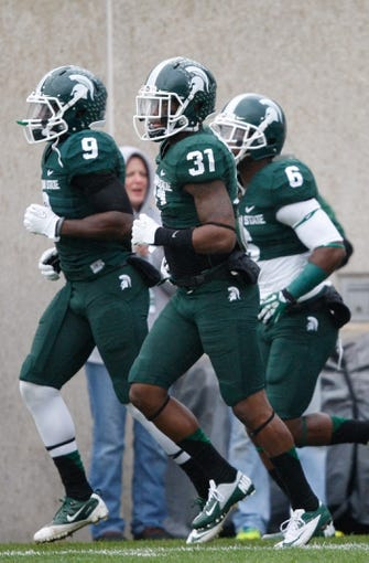Nov 2, 2013; East Lansing, MI, USA; Michigan State Spartans cornerback Darqueze Dennard (31) safety Isaiah Lewis (9) and cornerback Mylan Hicks (6) warm up before the game against the Michigan Wolverines at Spartan Stadium. The Spartans beat the Wolverines 29-6. Mandatory Credit: Raj Mehta-USA TODAY Sports