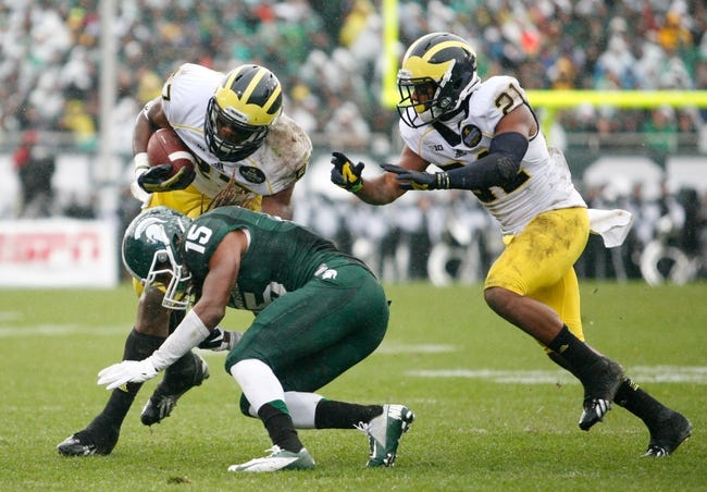 Nov 2, 2013; East Lansing, MI, USA; Michigan Wolverines tight end Devin Funchess (87) gets tackled by Michigan State Spartans cornerback Trae Waynes (15) during the second quarter at Spartan Stadium. The Spartans beat the Wolverines 29-6. Mandatory Credit: Raj Mehta-USA TODAY Sports