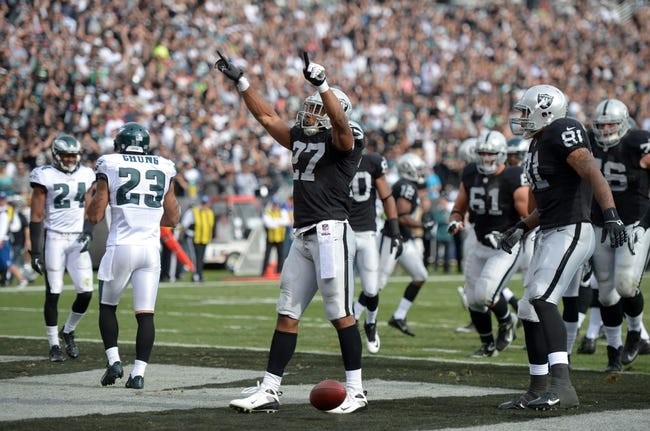 Nov 3, 2013; Oakland, CA, USA; Oakland Raiders running back Rashad Jennings (27) celebrates with tight end Mycal Rivera (81) after scoring on an 8-yard touchdown run against the Philadelphia Eagles at O.co Coliseum. The Eagles defeated the Raiders 49-20. Mandatory Credit: Kirby Lee-USA TODAY Sports