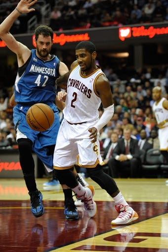 Nov 4, 2013; Cleveland, OH, USA; Cleveland Cavaliers point guard Kyrie Irving (2) dribbles along the baseline against Minnesota Timberwolves power forward Kevin Love (42) at Quicken Loans Arena. Cleveland won 93-92. Mandatory Credit: David Richard-USA TODAY Sports