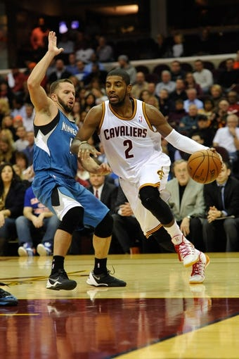 Nov 4, 2013; Cleveland, OH, USA; Cleveland Cavaliers point guard Kyrie Irving (2) drives past Minnesota Timberwolves point guard J.J. Barea (11) during a game at Quicken Loans Arena. Cleveland won 93-92. Mandatory Credit: David Richard-USA TODAY Sports