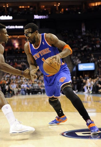 Nov 8, 2013; Charlotte, NC, USA; New York Knicks forward center Amar'e Stoudemire (1) drives into the paint as he is defended by Charlotte Bobcats forward Jeff Adrien (4) during the game at Time Warner Cable Arena. Mandatory Credit: Sam Sharpe-USA TODAY Sports