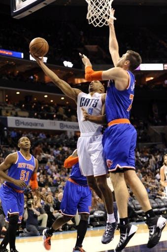 Nov 8, 2013; Charlotte, NC, USA; Charlotte Bobcats guard Gerald Henderson (9) drives to the basket and scores as he is defended by New York Knicks forward center Andrea Bargnani (77) during the game at Time Warner Cable Arena. Knicks win 101-91. Mandatory Credit: Sam Sharpe-USA TODAY Sports