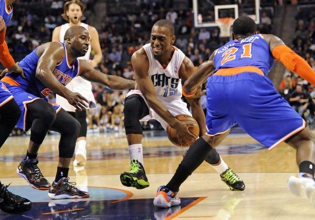 Nov 8, 2013; Charlotte, NC, USA; Charlotte Bobcats guard Kemba Walker (15) drives past New York Knicks guard Raymond Felton (2) and guard forward Iman Shumpert (21) during the game at Time Warner Cable Arena. Knicks win 101-91. Mandatory Credit: Sam Sharpe-USA TODAY Sports