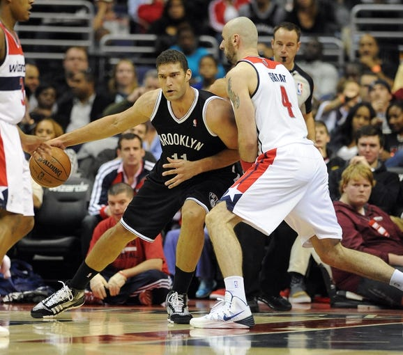 Nov 8, 2013; Washington, DC, USA; Brooklyn Nets center Brook Lopez (11) dribbles the ball as Washington Wizards center Marcin Gortat (4) defends during the first half at the Verizon Center. Mandatory Credit: Brad Mills-USA TODAY Sports