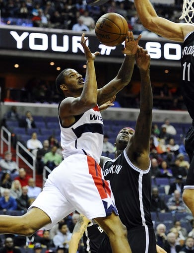 Nov 8, 2013; Washington, DC, USA; Washington Wizards small forward Trevor Ariza (1) has his shot blocked by Brooklyn Nets center Andray Blatche (0) during the first half at the Verizon Center. Mandatory Credit: Brad Mills-USA TODAY Sports