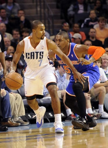 Nov 8, 2013; Charlotte, NC, USA; (Editors note: Caption correction) Charlotte Bobcats guard Ramon Sessions (7) looks to pass as he is defended by New York Knicks forward Metta World Peace (51) during the game at Time Warner Cable Arena. Mandatory Credit: Sam Sharpe-USA TODAY Sports