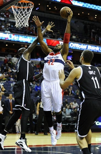 Nov 8, 2013; Washington, DC, USA; Washington Wizards power forward Nene Hilario (42) shoots over Brooklyn Nets power forward Kevin Garnett (2) and Brooklyn Nets center Brook Lopez (11) during the first half at the Verizon Center. Mandatory Credit: Brad Mills-USA TODAY Sports