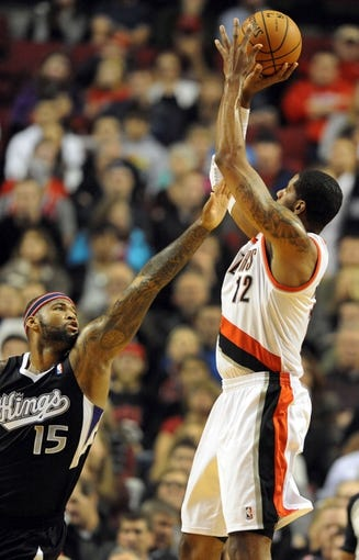 Nov 8, 2013; Portland, OR, USA; Portland Trail Blazers power forward LaMarcus Aldridge (12) shoots over Sacramento Kings center DeMarcus Cousins (15) during the first quarter of the game at the Moda Center. Mandatory Credit: Steve Dykes-USA TODAY Sports