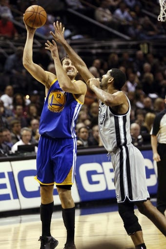 Nov 8, 2013; San Antonio, TX, USA; Golden State Warriors center Andrew Bogut (left) takes a shot over San Antonio Spurs forward Tim Duncan (right) during the second half at AT&T Center. The Spurs won 76-74. Mandatory Credit: Soobum Im-USA TODAY Sports