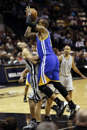 Nov 8, 2013; San Antonio, TX, USA; San Antonio Spurs guard Manu Ginobili (left) draws a charge from Golden State Warriors forward Marreese Speights (right) during the second half at AT&T Center. The Spurs won 76-74. Mandatory Credit: Soobum Im-USA TODAY Sports