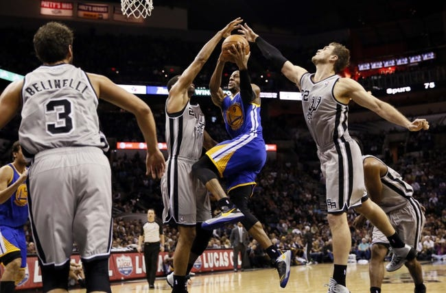 Nov 8, 2013; San Antonio, TX, USA; Golden State Warriors forward Andre Iguodala (9) drives for the basket between San Antonio Spurs forward Tim Duncan (21) and Tiago Splitter (22) during the second half at AT&T Center. The Spurs won 76-74. Mandatory Credit: Soobum Im-USA TODAY Sports