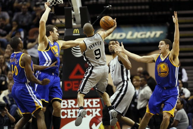 Nov 8, 2013; San Antonio, TX, USA; San Antonio Spurs guard Tony Parker (9) passes the ball to forward Tim Duncan (21) during the second half against the Golden State Warriors at AT&T Center. The Spurs won 76-74. Mandatory Credit: Soobum Im-USA TODAY Sports