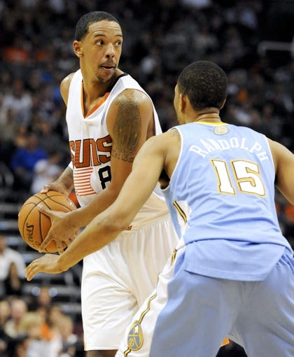 Nov 8, 2013; Phoenix, AZ, USA; Phoenix Suns power forward Channing Frye (8) prepares to pass the ball under pressure from Denver Nuggets power forward Anthony Randolph (15) during the fourth quarter at US Airways Center. The Suns defeated the Nuggets 114-103. Mandatory Credit: Casey Sapio-USA TODAY Sports