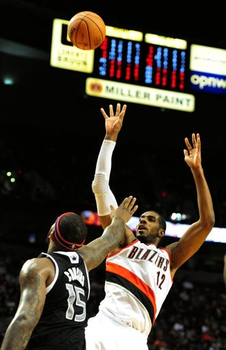 Nov 8, 2013; Portland, OR, USA; Portland Trail Blazers power forward LaMarcus Aldridge (12) scores over Sacramento Kings center DeMarcus Cousins (15) during the fourth quarter of the game at the Moda Center. The Blazers won the game 104-91. Mandatory Credit: Steve Dykes-USA TODAY Sports