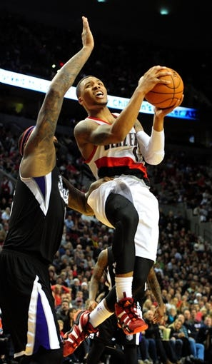 Nov 8, 2013; Portland, OR, USA; Portland Trail Blazers point guard Damian Lillard (0) drives to the basket on Sacramento Kings center DeMarcus Cousins (15) during the fourth quarter of the game at the Moda Center. The Blazers won the game 104-91. Mandatory Credit: Steve Dykes-USA TODAY Sports