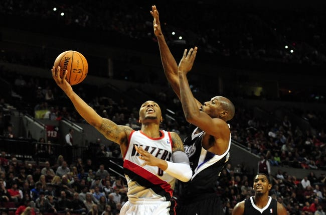 Nov 8, 2013; Portland, OR, USA; Portland Trail Blazers point guard Damian Lillard (0) drives to the basket on Sacramento Kings small forward Travis Outlaw (25) during the fourth quarter of the game at the Moda Center. The Blazers won the game 104-91. Mandatory Credit: Steve Dykes-USA TODAY Sports