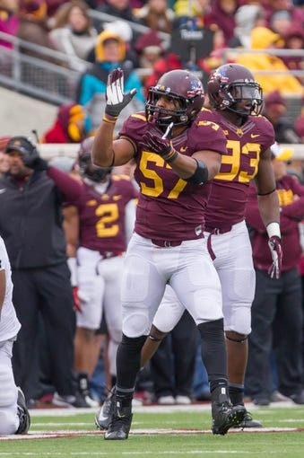 Nov 9, 2013; Minneapolis, MN, USA; Minnesota Gophers linebacker Aaron Hill (57) claps at the crowd in the third quarter against the Penn State Nittany Lions at TCF Bank Stadium. Minnesota wins 24-10. Mandatory Credit: Brad Rempel-USA TODAY Sports