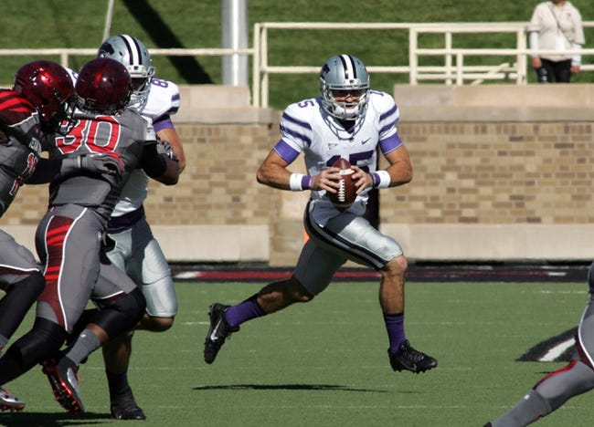 Nov 9, 2013; Lubbock, TX, USA; Kansas State Wildcats quarterback Jake Waters (15) looks for an open receiver against the Texas Tech Red Raiders in the first half at Jones AT&T Stadium. Mandatory Credit: Michael C. Johnson-USA TODAY Sports