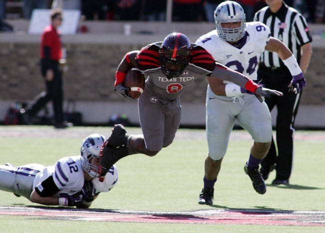 Nov 9, 2013; Lubbock, TX, USA; Texas Tech Red Raiders running back SaDale Foster (8) is tackled by Kansas State Wildcats free safety Ty Zimmerman (12) during the first half at Jones AT&T Stadium. Mandatory Credit: Michael C. Johnson-USA TODAY Sports